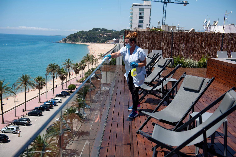 Empleada limpia la barandilla de la terraza de un hotel de Lloret de Mar. Foto: Josep Lago/AFP