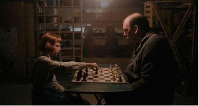 Beth Harmon y Bill Bates durante su primera partida de ajedrez en el sótano. NETFLIX